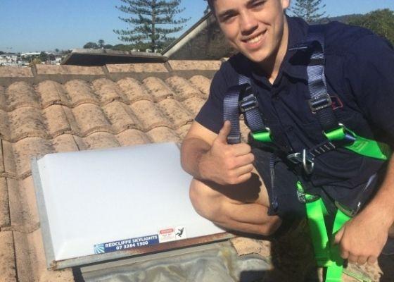 RTL Tradesmen poses next to newly installed skylight