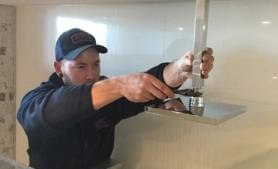 Plumber from RTL Trades fixing broken plumbing inside Brisbane home