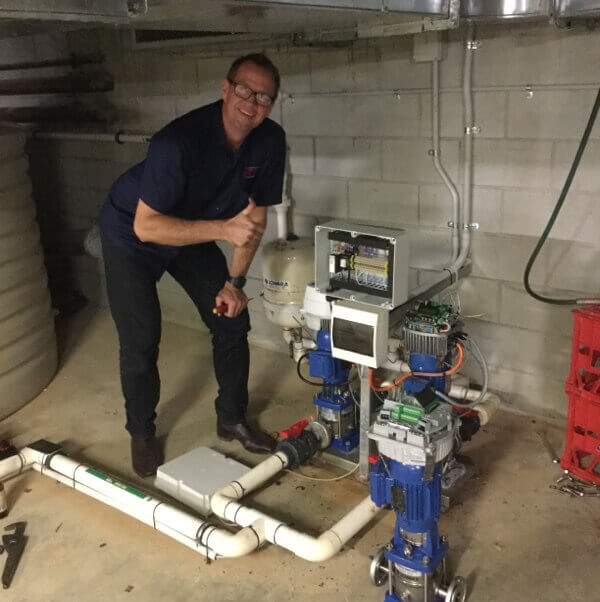electrician in basement of home checking pump system and fixing errors